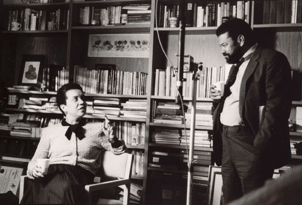 Henry Hampton stands in the right of the photo dressed in a suit and tie with a paper cup in-hand while speaking with a seated Marian Wright Edelman, also dressed sharply in a blouse and long skirt.
