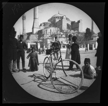 William Sachtleben's Humber bicycle at rest in Constantinople draws a crowd of spectators. Background: Hagia Sophia and Thomas Allen on his bicycle. March 21, 1891.