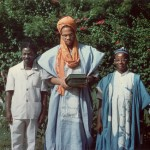 Malcolm in Accra, Ghana, May 1964, holding the Koran given to him by Alhaji Isa Wali, Nigerian High Commissioner to Ghana (right). Photo by Alice Windom.