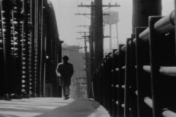 Photo of a man walking down a street lined with telephone polls from More than One Thing.