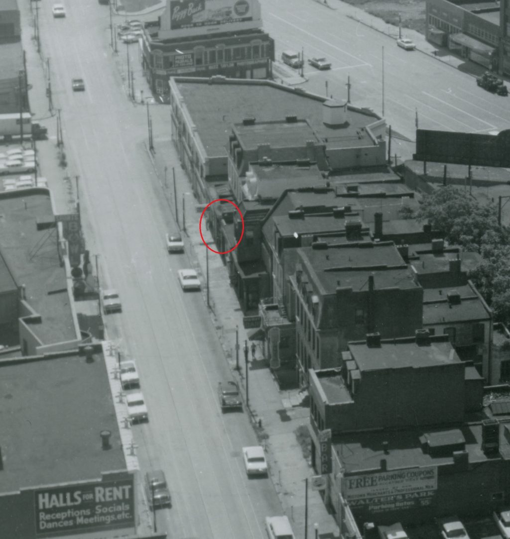 Image 2: An aerial view of the 3500 block of Olive in the early 1960s, taken from the Continental Life Building looking toward the southeast. The location of Dante's Inferno, the earliest known gay bar on the block, is circled in red. Dante's Inferno had closed about a decade before this photograph was taken, but the exterior of the building probably remained more or less the same. Image courtesy of the Missouri History Museum.
