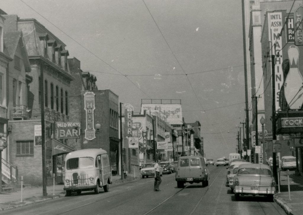 Image 6: The 3500 block of Olive looking west toward Grand in the early 1960s. Shelley's Midway Bar and the Golden Gate Bar are visible on the left side of the street. The Onyx Room is where the Schlitz sign can be seen farther down the street on the left. Image courtesy of the Missouri History Museum.