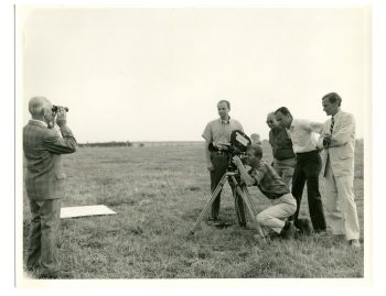 A photo depicting a group of five men huddled around a camera (left) with William Gaddis (far right), all working on the U.S. army film, The Battle of St. Vith.
