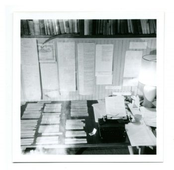A photo of William Gaddis' workroom. The desk and wall are covered with intricately laid out, typed papers; there are books on shelves in the very top of the photo frame; and a typewriter with a lamp rests on the right of the desk.