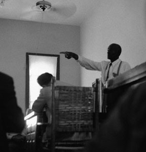 "22 Sep 1955, Sumner, Mississippi, USA --- This dramatic courtroom scene shows 64-year-old ""Uncle Mose"" Wright, Grand-Uncle of murdered Emmett Till, 14-year-old Negro boy, as he stood up in the packed chamber and pointed a finger at defendants, Roy Bryant and John W. Milan. In answer to a question asking him to identify the man who came to his home on the night of August 28 and took young Till away with them, Wright pointed and answered, ""There they are."" The victims mother, Mrs. Mamie Bradley, is scheduled to testify today. --- Image by © Bettmann/CORBIS"