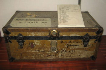 """The image displays an worn footlocker, or luggage trunk. The trunk has """"Dan Bartlett St Louis MO"""" written on the lid, along with a number of other, worn scribbles along its front."""