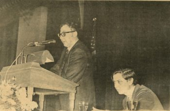 A photo of Stanley Elkin speaking at a podium while William Gass, also on-stage, looks on.