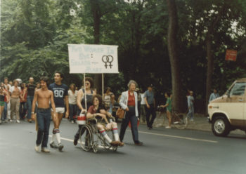 Groups of people walking down the middle of the street during the Sea Cliff Pride Parade. In the foreground of the photo are five individuals, four walking abreast of each other and one in a wheelchair. A sign attached to the wheelchair with poles is mostly illegible, but does have two female gender symbols side-by-side.