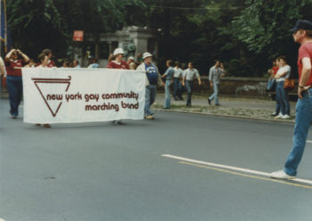 """Groups of people walking down the middle of the street holding a banner during the Sea Cliff Pride Parade. The banner reads """"New York Gay Community Marching Band."""""""