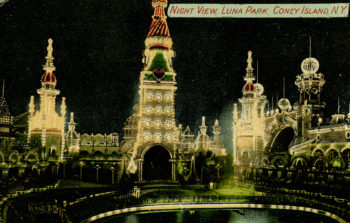 """The front image of a postcard. Text on the image designates it as """"Night view, Luna Park, Coney Island, NY"""" and the photo is of the towers and spires at Coney Island, brightly lit at night by a multitude of fairy-lights."""