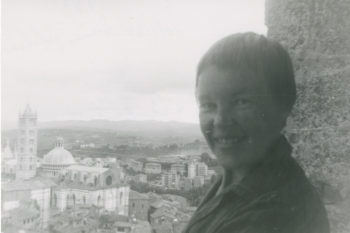 May Swenson smiling at the camera with an expanse of Siena, Italy, in the background.