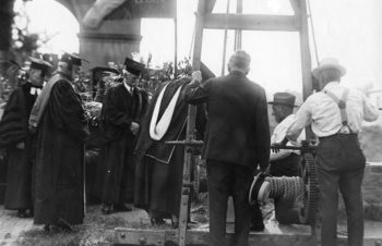 The photo shows that the 1923 ceremonial laying of the cornerstone of Duncker Hall was attended by four men in ceremonial robes, one in a nice suit and hat, and was lowered into the foundation by two workers in suspenders using a rope system.