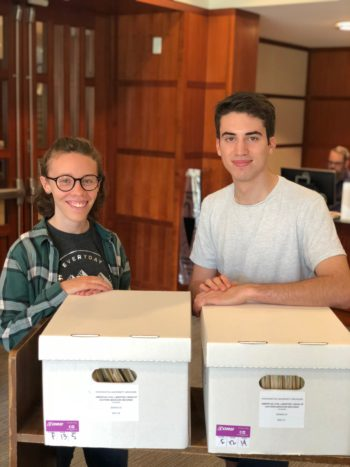 WUSTL undergraduates Natalie Hilmer and Jordan Dubin stand with boxes from the archive.