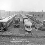 trolley cars parked outside the factory of St. Louis car company with railroad tracks in front and caption on image