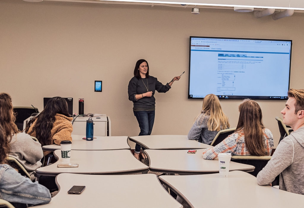 Amanda Albert is standing in front of a large digital screen showing instruction notes while a mix of six students sit listening.