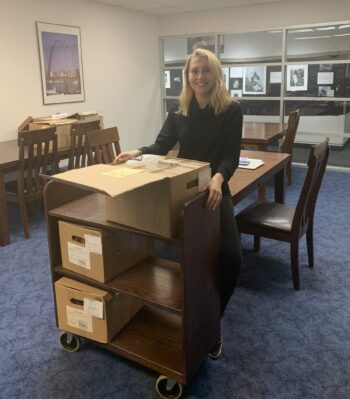person standing behind cart of archive boxes in a library