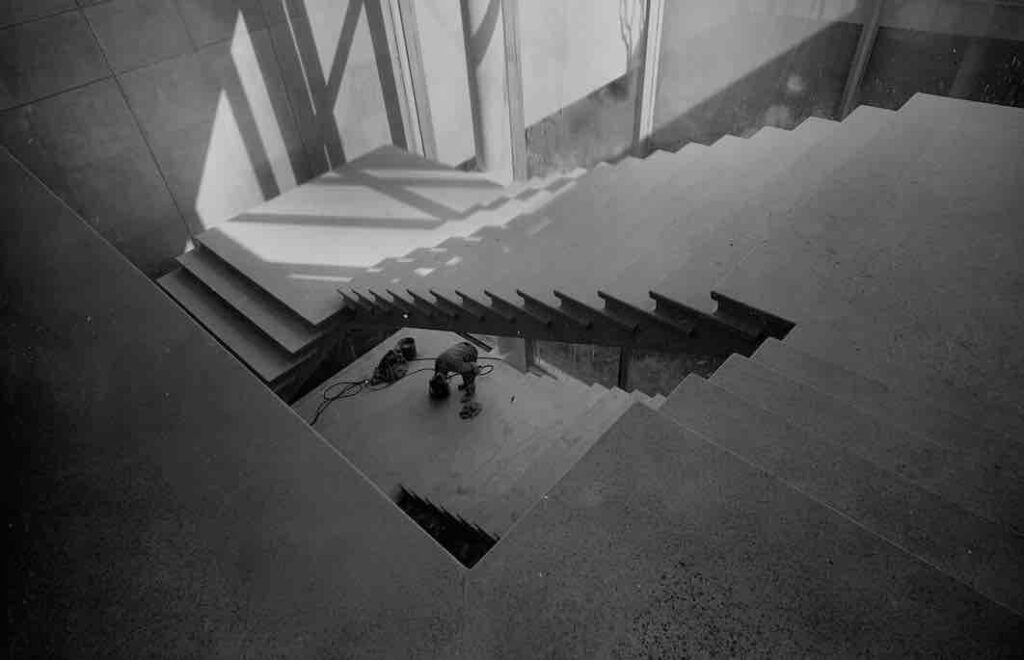 Construction shot of the Andrew and Jayne Kagan Grand Staircase. The cement is poured and the stairs are structurally sound in this photo, as demonstrated by the lone figure of a workman, but there are no railings or other finishing touches.