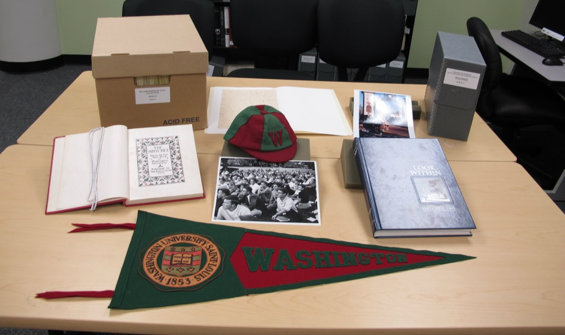 A small collection box with its contents displayed on the table. The Collection consists of Washington University items from the past - there is an older flag and sports cap in the WashU colors; a text open to a highly stylized bookplate with a placeholder ribbon; a thicker, leather-bound text; some photographs; a glossy pamphlet; and a smaller collection box that typically holds papers or lose documents.