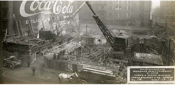 A photo of a crane amongst a construction site with building materials while a horse and carriage trot in the street. The site is to be an office building for the Monward Realty Company and was designed by Eames & Young, whose collection the Libraries' hold. The photo is dated 1913.
