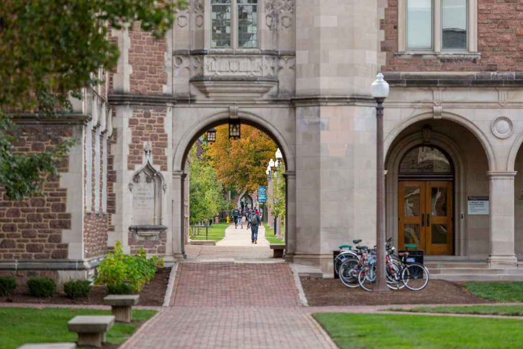Decorative image of students walking through one of the many arches on campus.