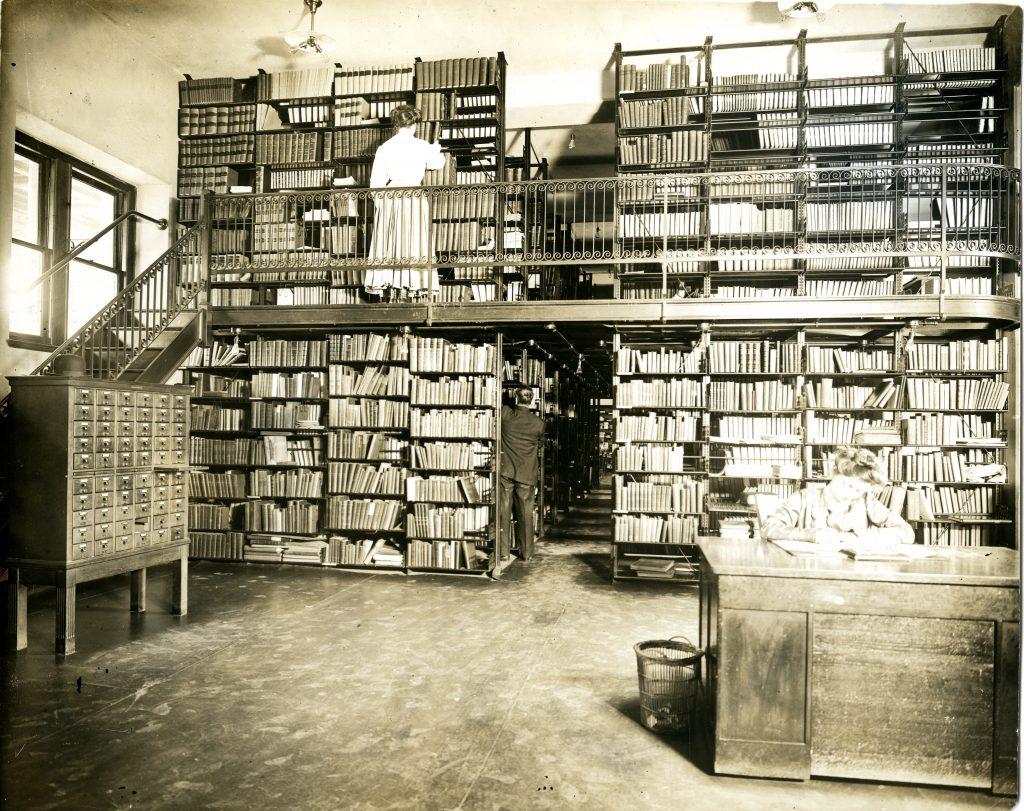 A historical photo of a librarian reshelving books at Ridgley Library circa 1910.