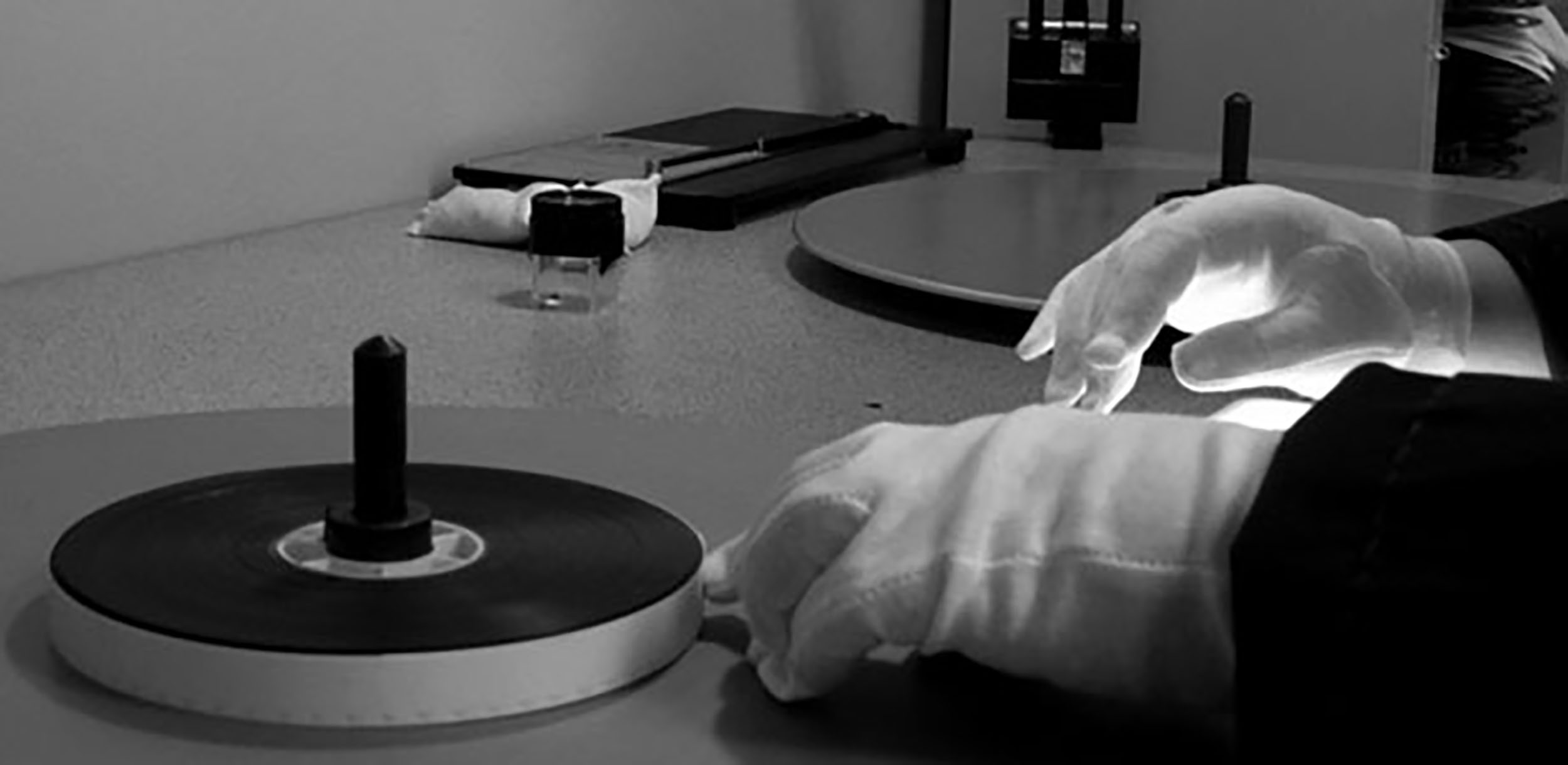 Cloth-gloved hands are readying a film on a reel.