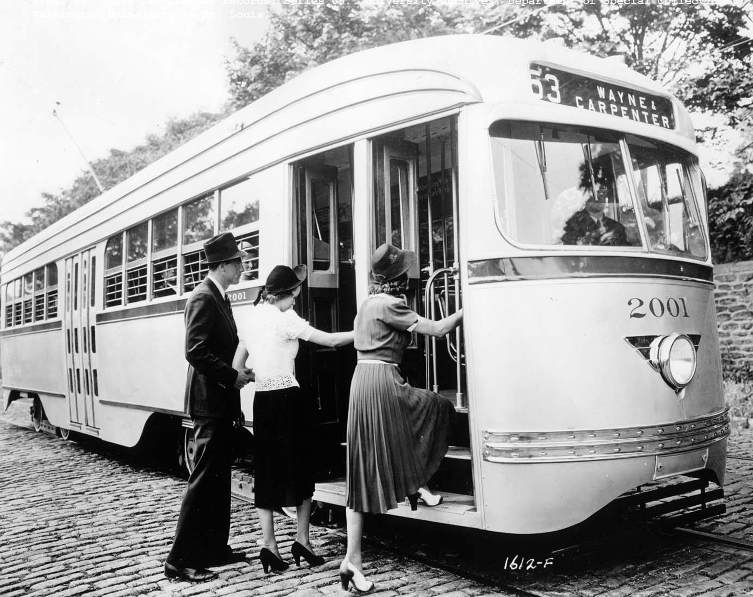 A black and white photo of a gentleman in a top hat helping two ladies off the cobblestone street and onto the Wayne & Carpenter #63 Streetcar in Saint Louis.