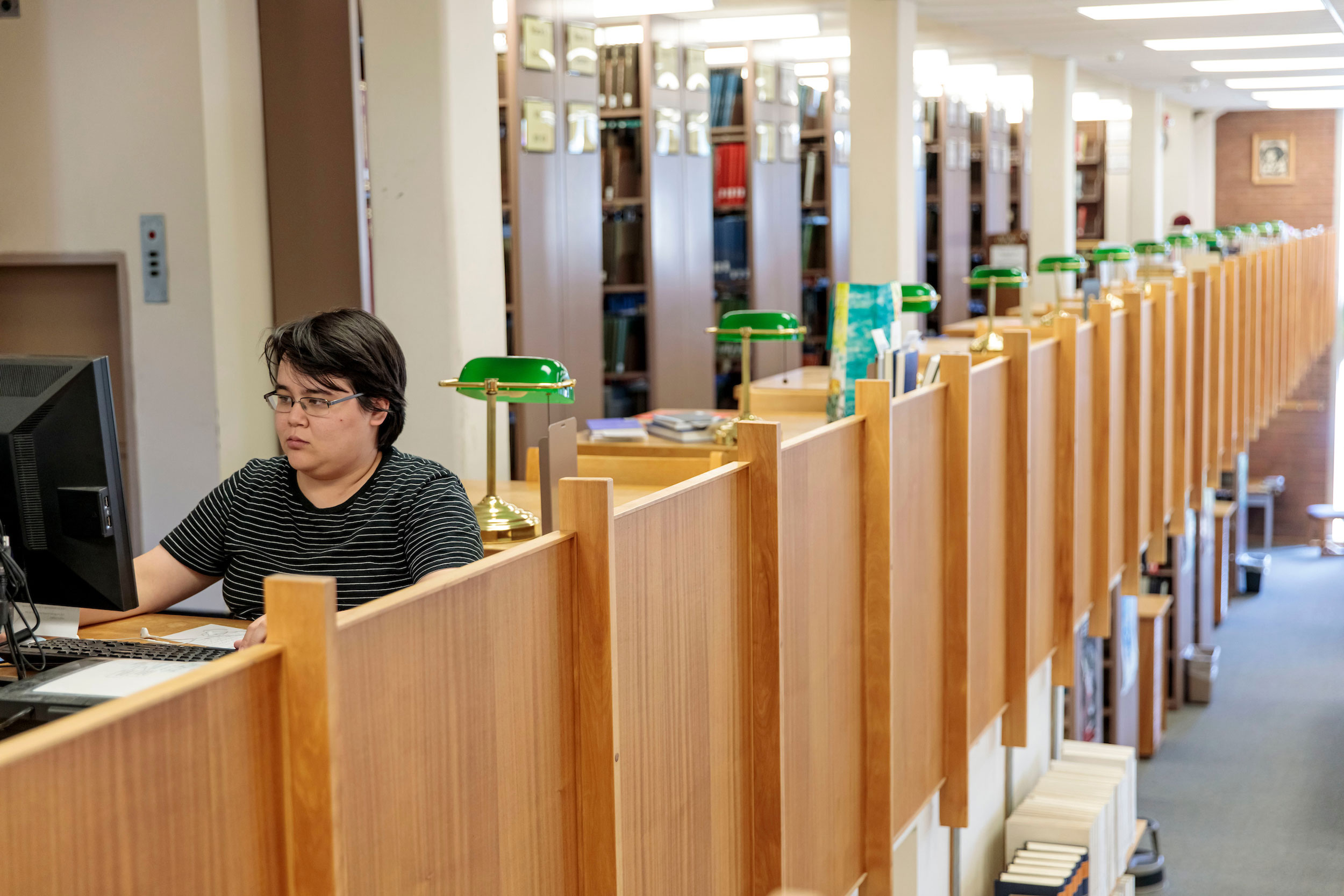 Student using a computer terminal near study cubbies in the Library book stacks.