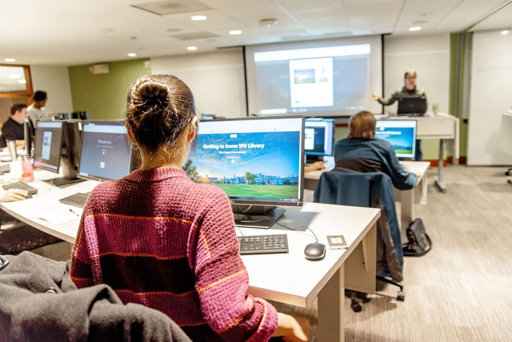Students sitting in a computer lab classroom for data management training.