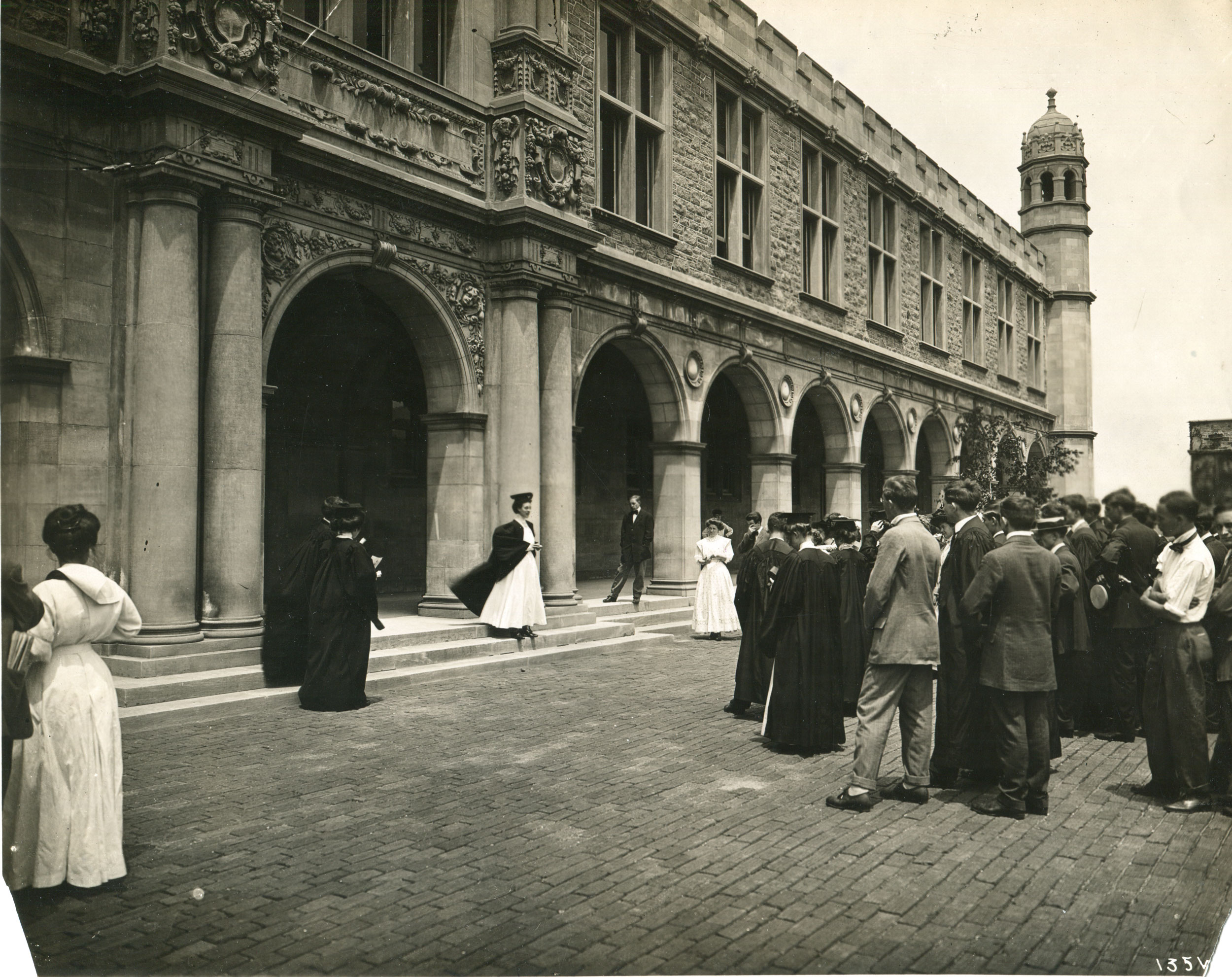 The photo shows a group of graduates and others celebrating commencement. A female student stands at the center beneath the archway entrance to Ridgely Hall being photographed in a white gown and commencement robes.