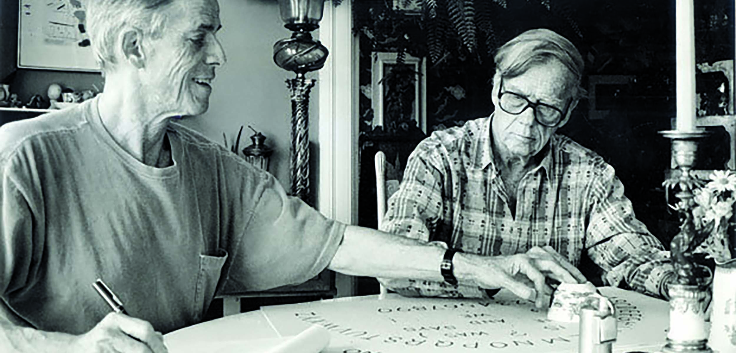 James Merrill and Langdon Hammer sat in front of an Ouija Board. Both Merrill and Hammer are touching the planchette used to communicate via Ouija and Merrill holds a pen ready for notes in his opposite hand.