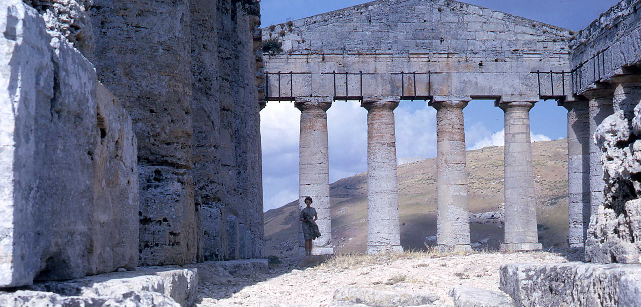 A woman in a skirt standing in the foreground amongst the ruins of the Greek Segesta Temple.