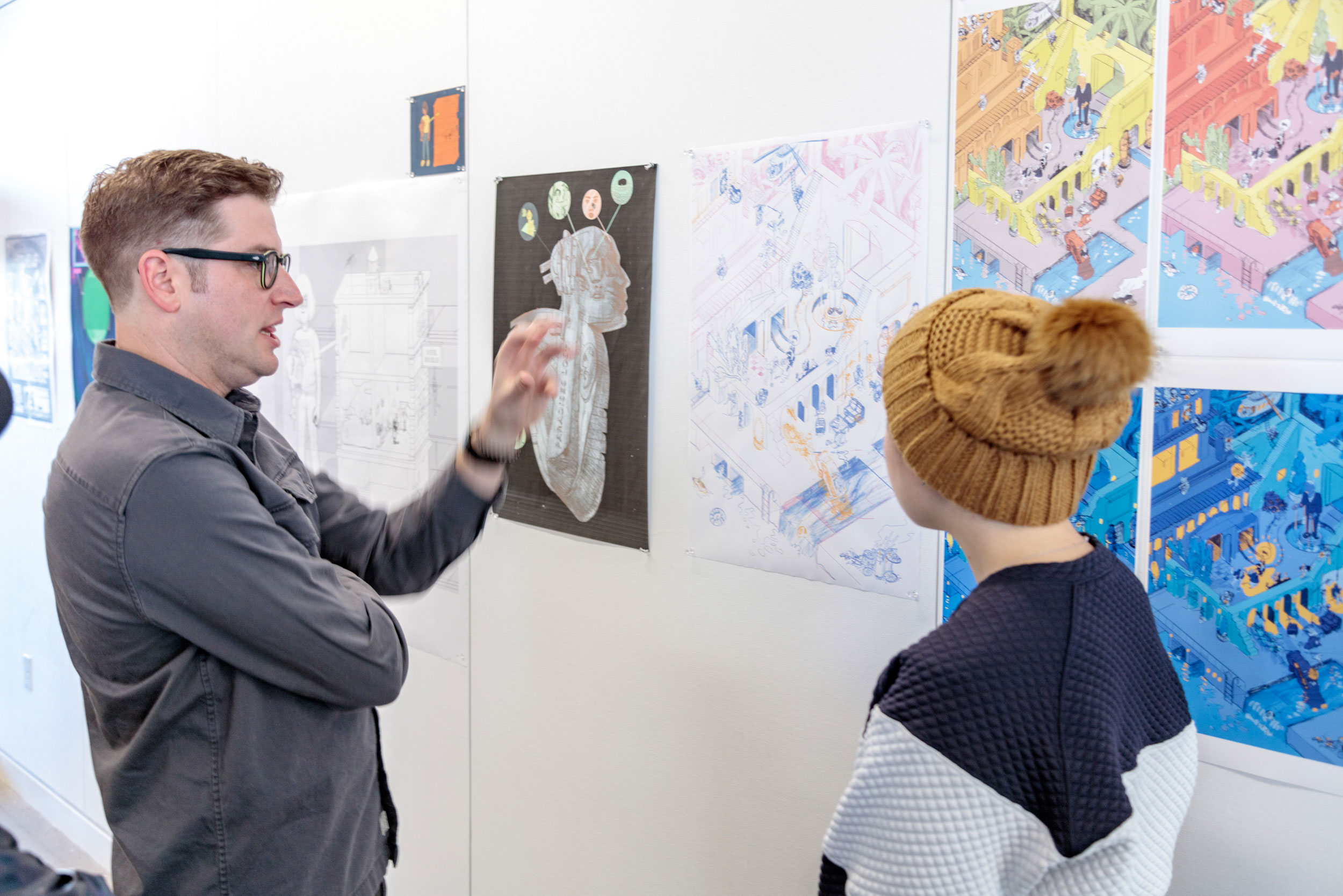 A faculty member and student discussing an art installation.