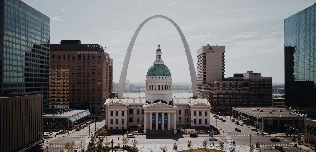 The Old St. Louis County Courthouse in downtown St. Louis, MO, with the Arch surrounding it in the background.