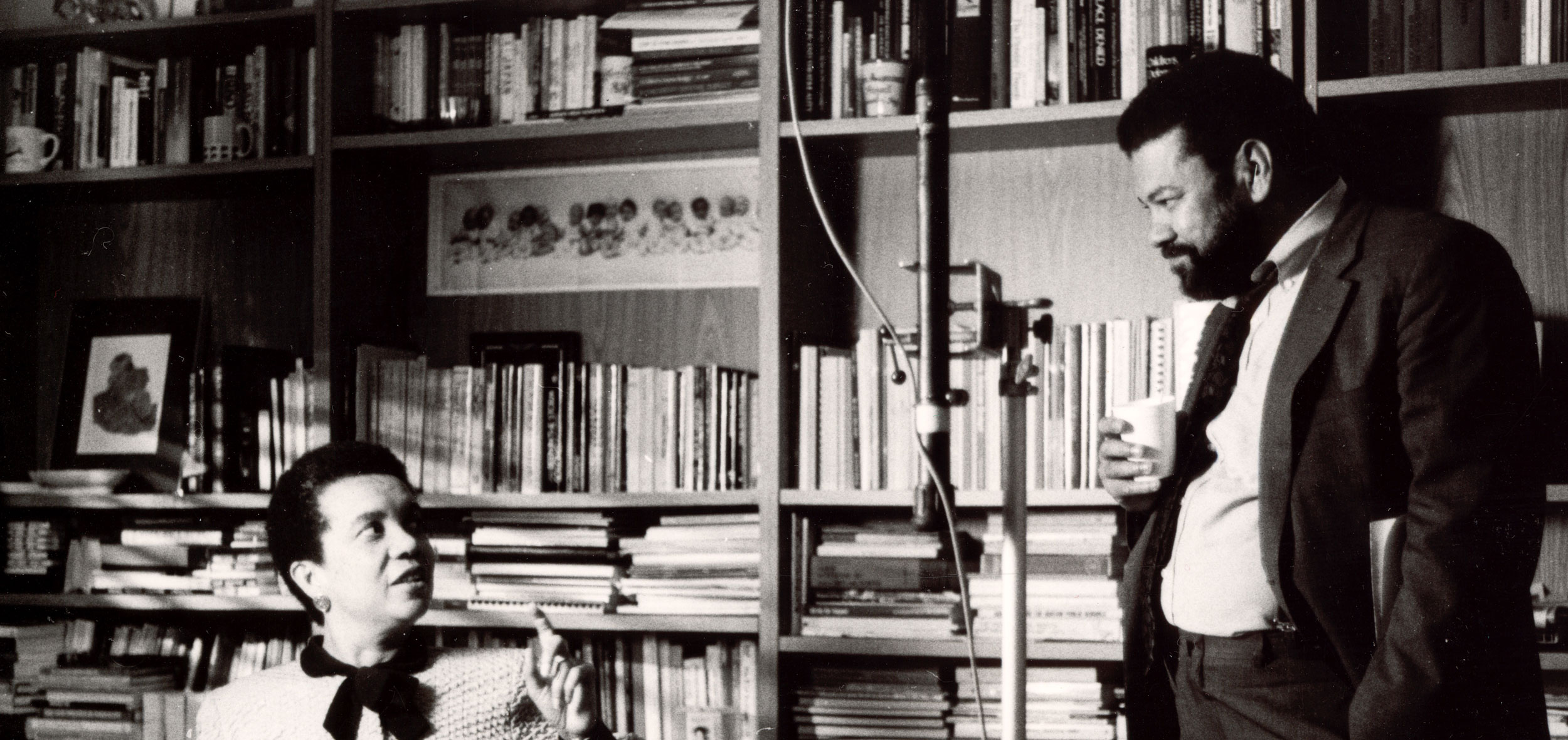 Filmmaker Henry Hampton stands in front of a heavily occupied bookshelf with a seated Marian Wright Edelman nearby.