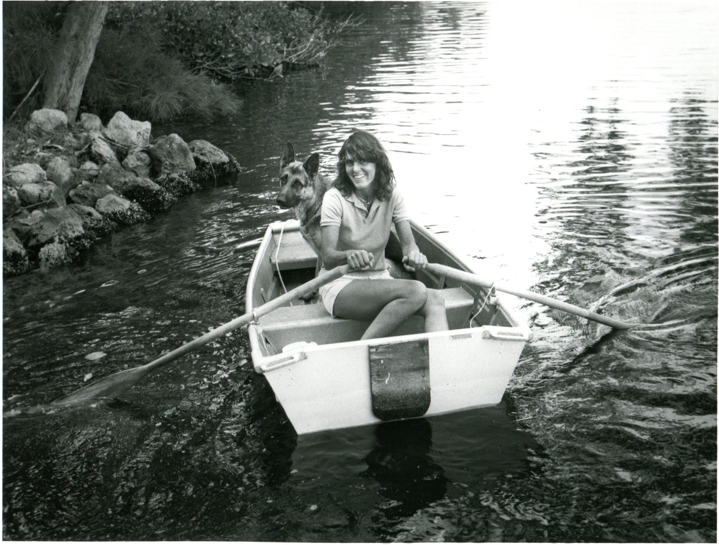 Joy Williams wears a collared t-shirt with white shorts and shoulder length hair as she sits in a small rowboat holding herself and her dog, a German Shepherd.