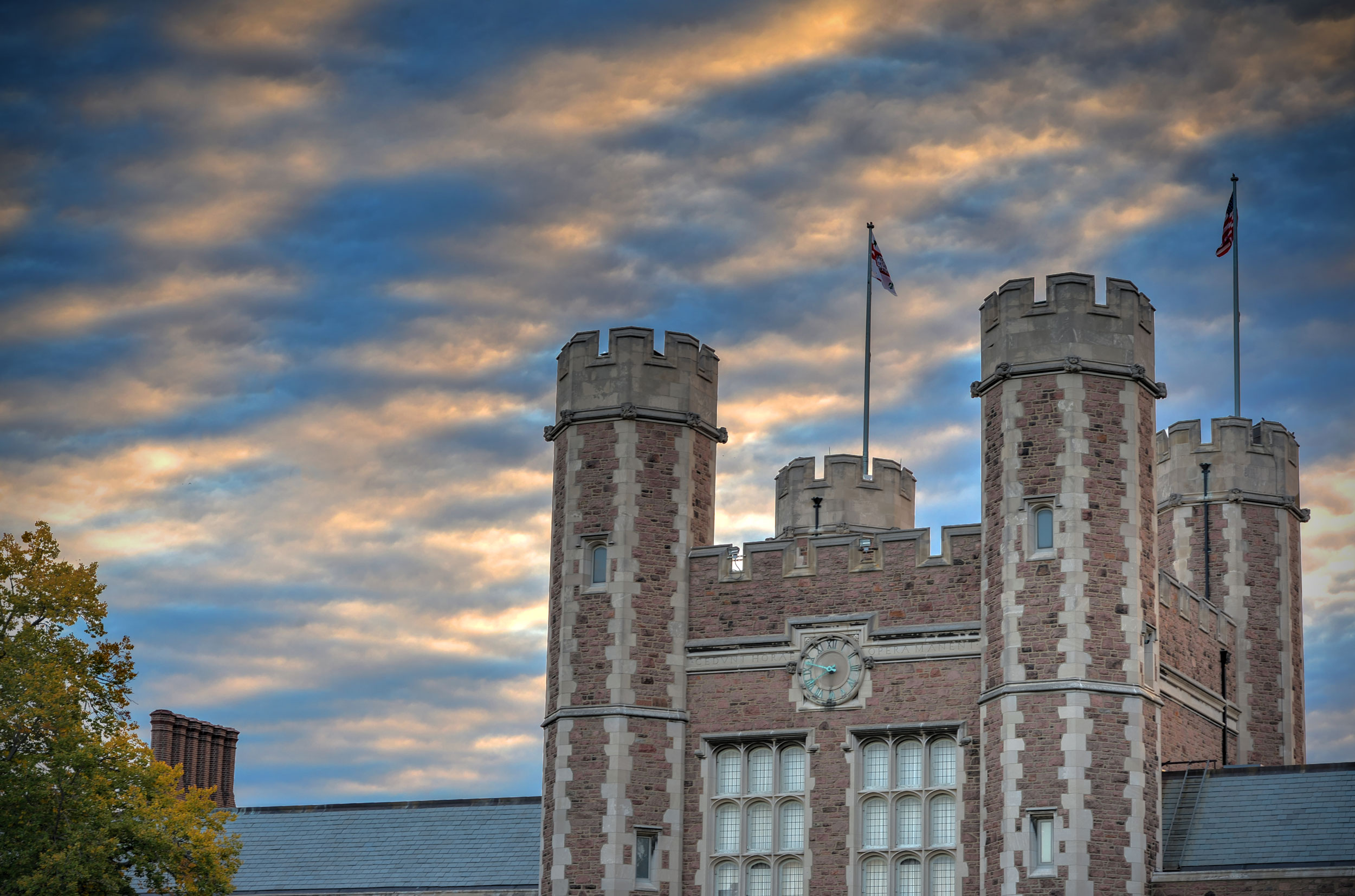The towers of Brookings Hall against a cloudy sky at dusk.