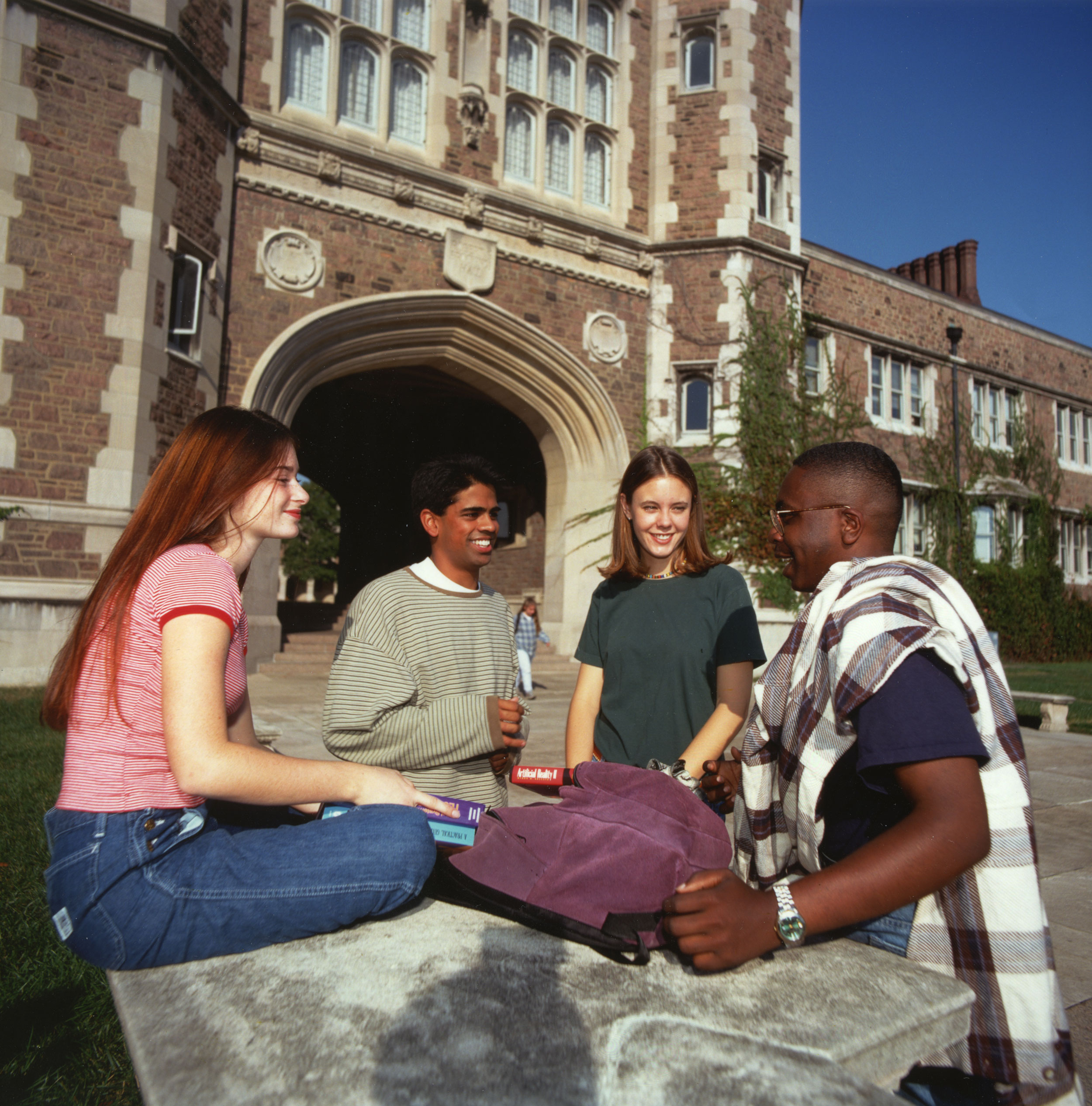 A group of four students gathered on the quad.