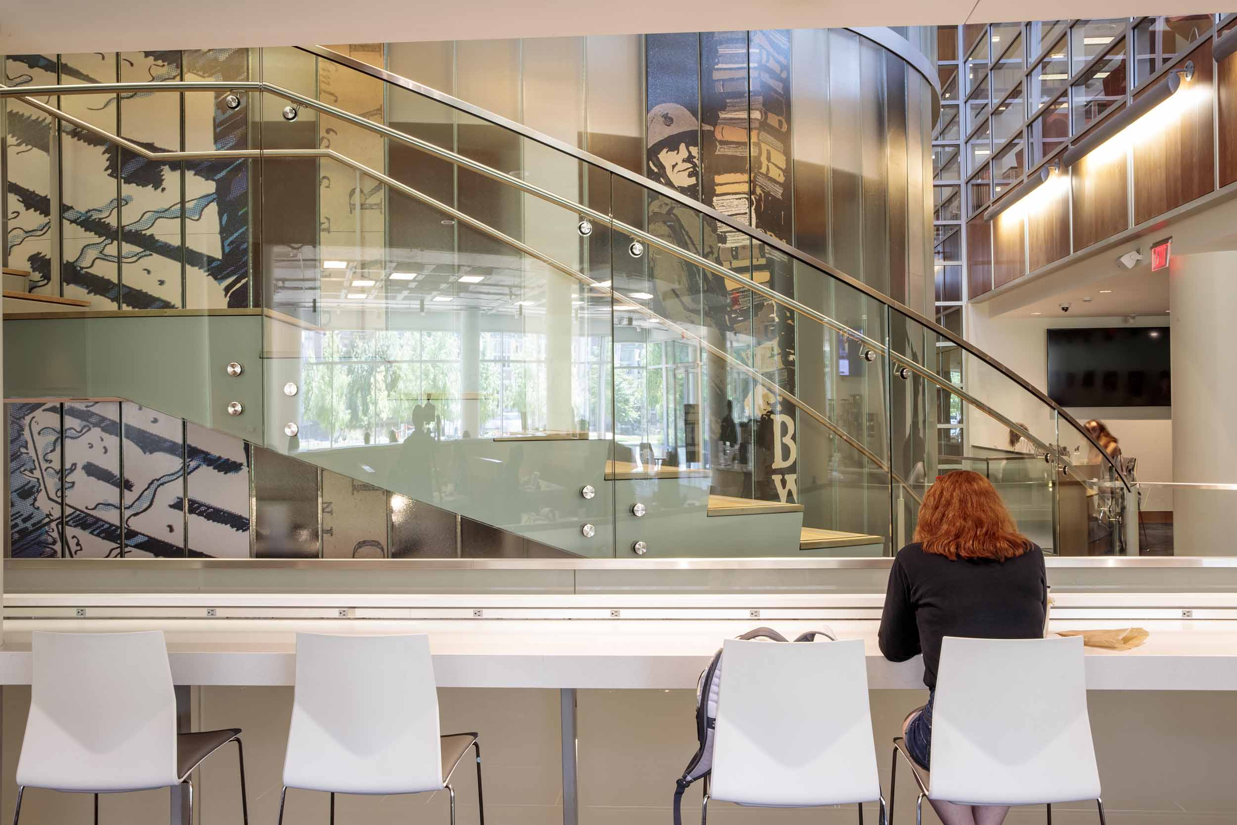A student studies at the bar seating area of Whispers Cafe with a view of the Newman Tower stairs in the background.