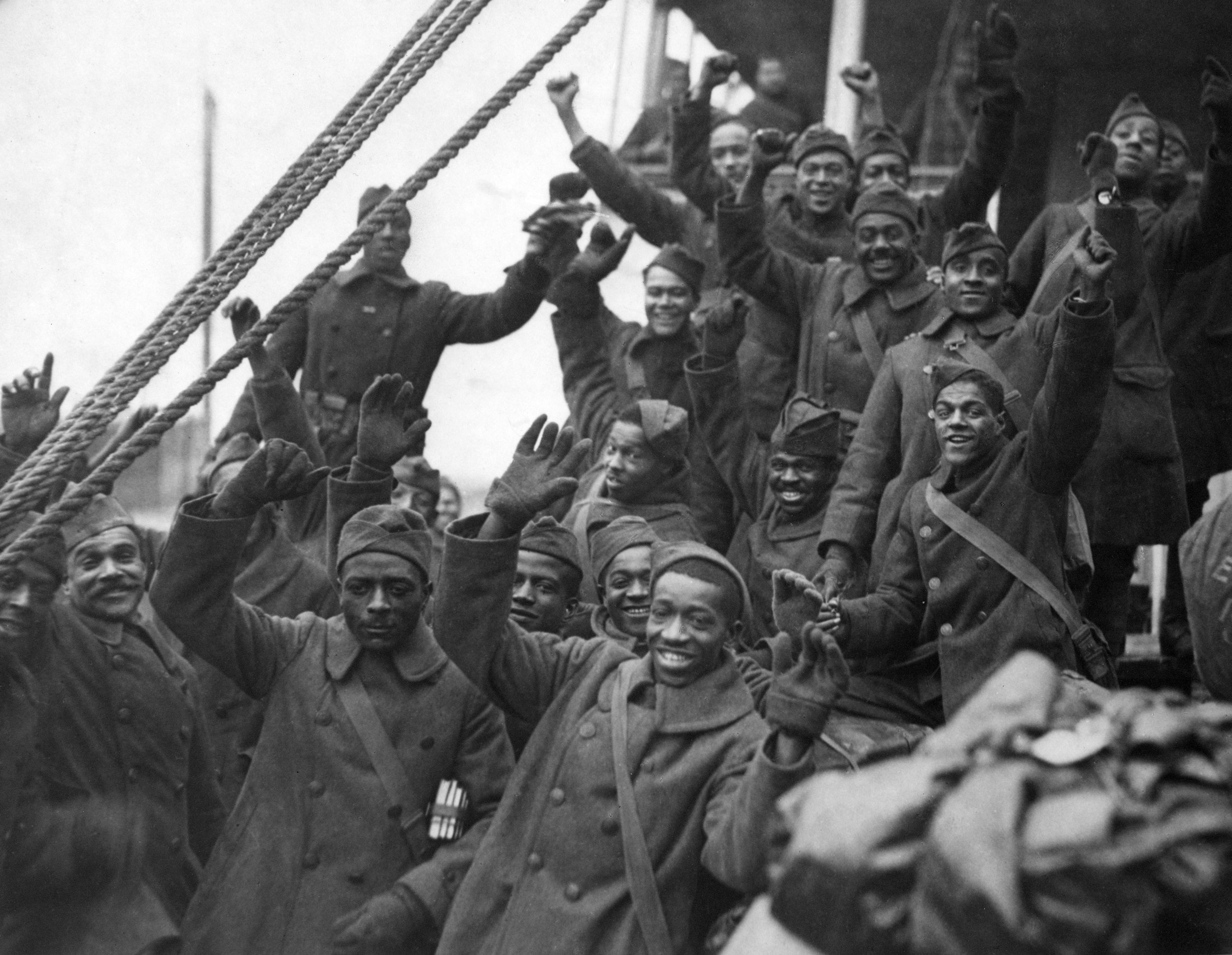 The Harlem Hellfighters in peacoats with arms raised in a cheer.