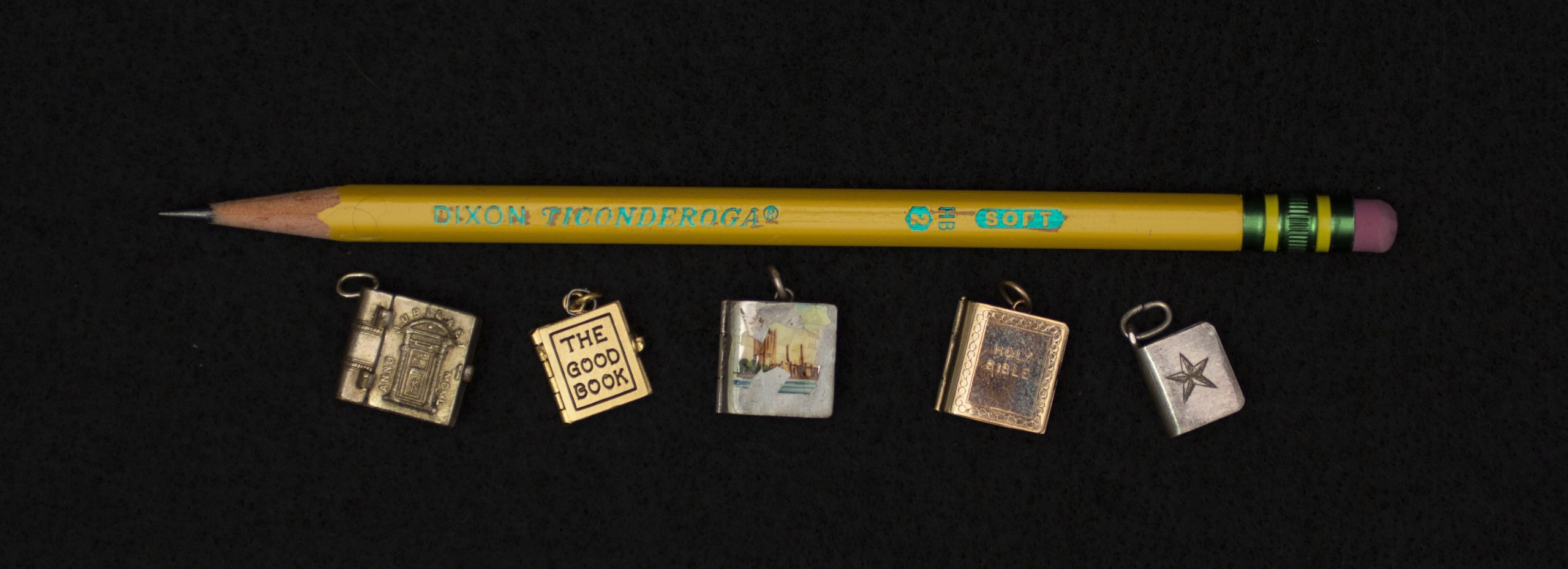 Five of the miniature books shown alongside a used #2 pencil. All five books fit along the length of the pencil with room to spare.