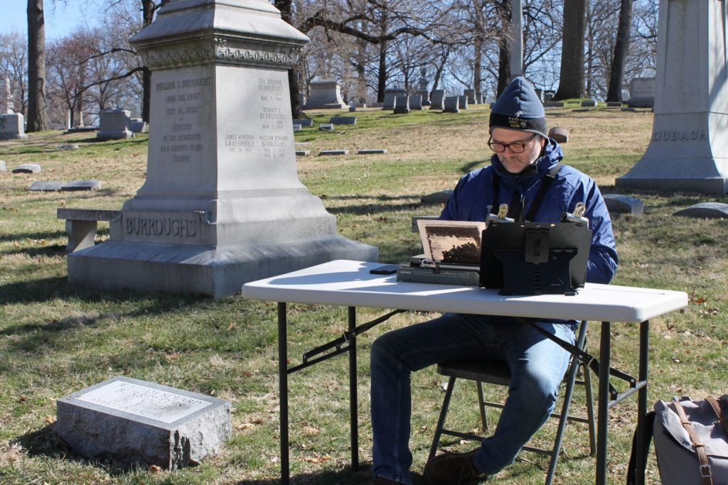 Tim Youd in Bellefontaine Cemetery sitting at a collapsable table and chair retyping Naked Lunch.