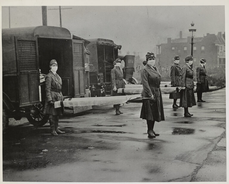 Female volunteers with the St. Louis Red Cross on duty, Oct. 1918, during the influenza epidemic. (Library of Congress, LC-DIG-ds-01290). In the photo, four teams of nurses in uniform with surgical masks covering their faces stand at the ready on either end of stretchers.