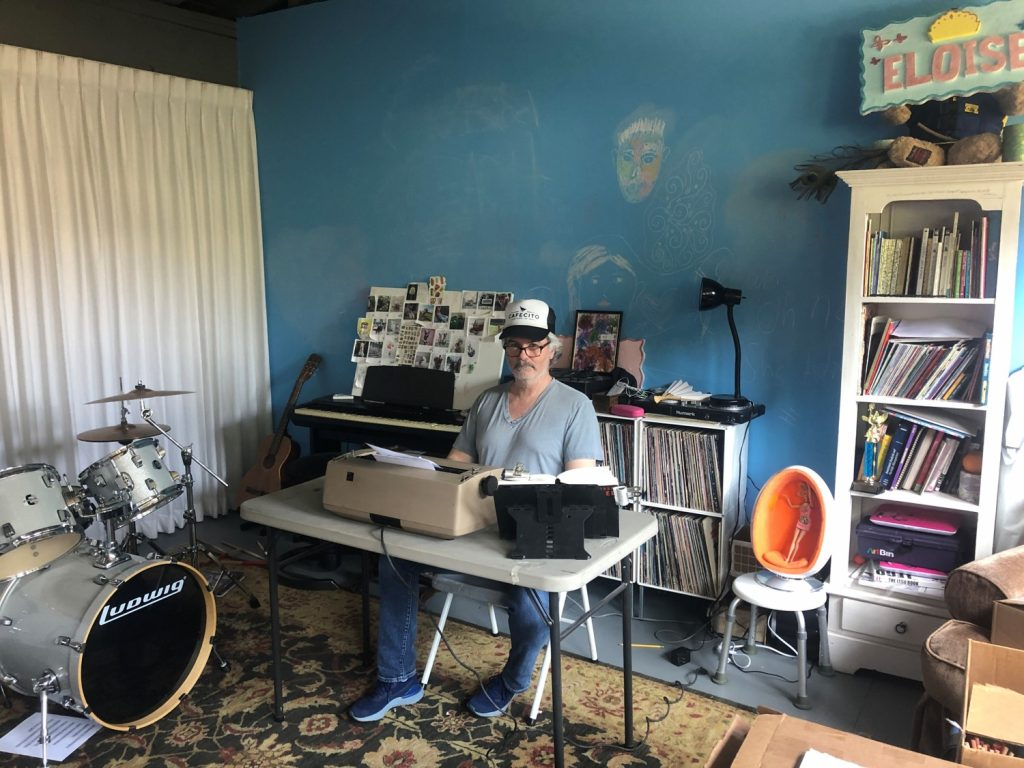 Youd sitting at a collapsable table with a typewriter retyping The Tunnel in his garage/studio. The Garage has a curtain partition set up, along with a rug on the floor, bookshelves, and a drum set, amongst other things.