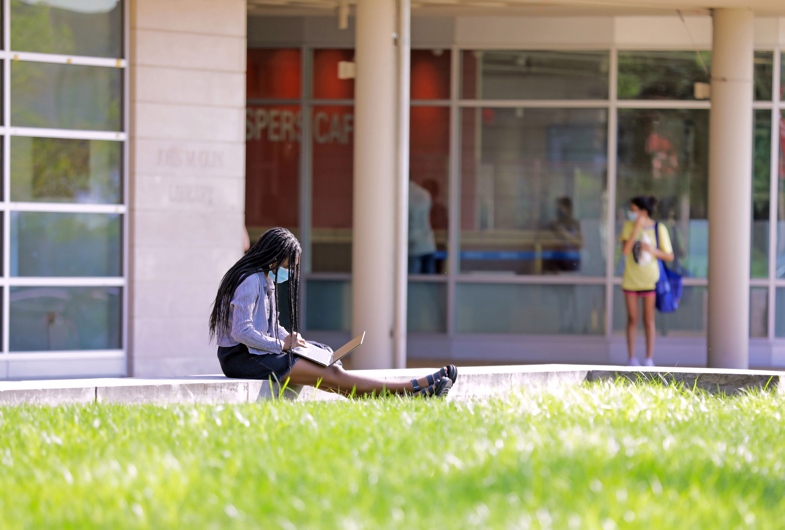 A student sitting and working on their laptop while masked outside of Olin Library.