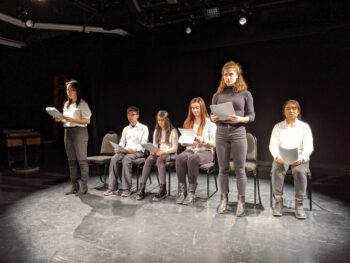 """Six students with six chairs in a row performing """"The Conscious Inexistence"""" on a spotlight lit stage. The first and fifth students are standing while reading from scripts in their hands."""