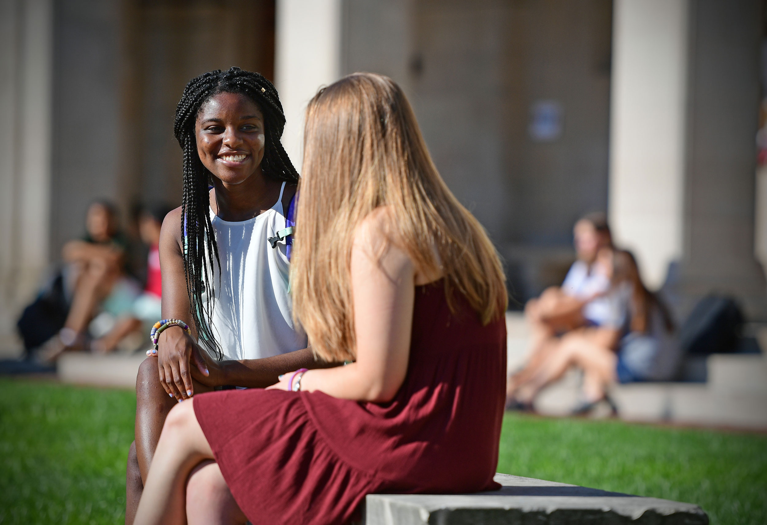 Two female presenting students talking at a bench on campus.