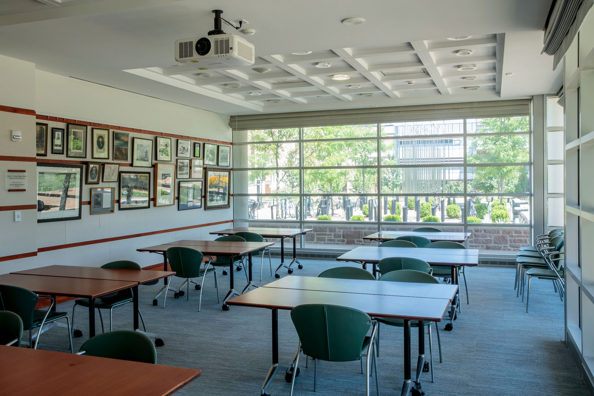 The Mendle Classroom has smaller, two-person tables and hosts a projector within the room. The space itself is large with many of the walls featuring ceiling windows.
