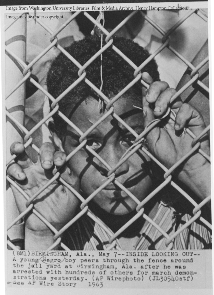 "Young boy behind a chainlink fence. The caption reads ""Birmingham, Ala., May 7. Inside Looking Out. A young Negro boy peers through the fence around the jail yard at Birmingham, Ama., after he was arrested with hundreds of others for march demonstrations yesterday."""