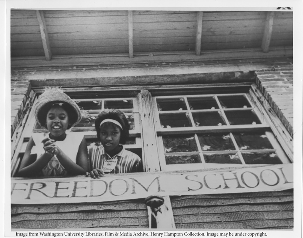 "Two young girls with their hair nicely done and in pressed tops peer out of a double window with a banner beneath them reading ""Freedom School."""